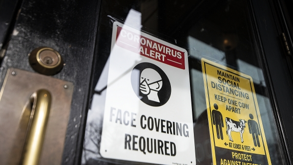 "A sign on a clear glass door says ""Face Covering Required."""