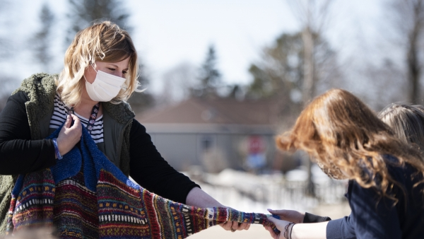 A woman in a face mask holds the arm of a sweater out to students who reach out and touch it.