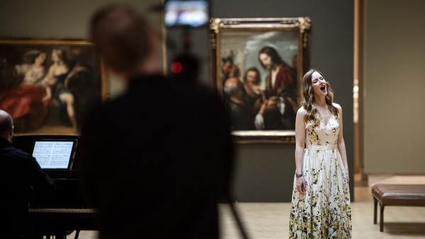 A singer in a long white floral gown tilts her head back as she belts a note surrounded by paintings in a museum.