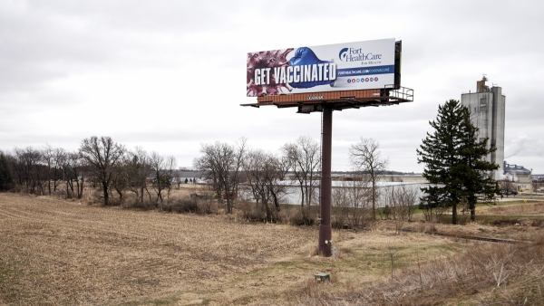 "A billboard shows the words ""Get Vaccinated."""