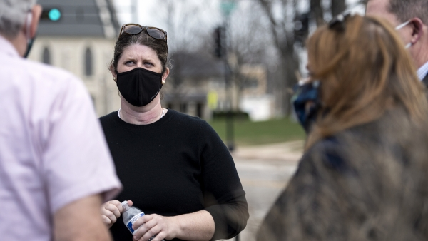 A woman in a black face mask speaks to people outside.