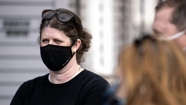 A woman in a face mask attends a campaign event outside.