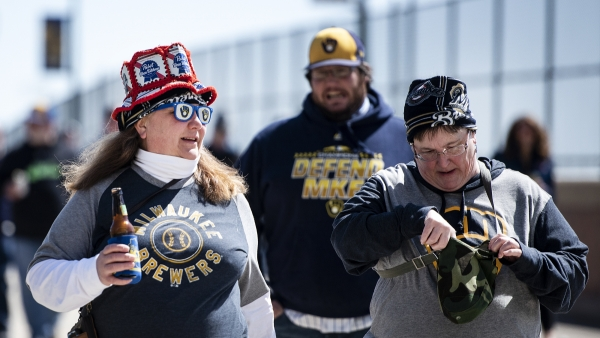 A fan wears a glasses with the Brewers logo, a hat made of PBR boxes and a Brewers shirt as she holds a beer walking into the stadium.