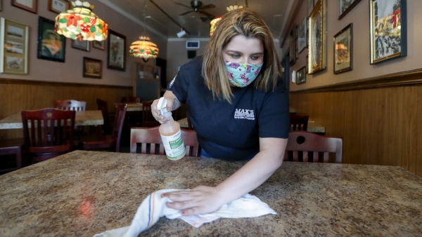 Sara Kennely, cleans one of the dining tables at Max's Allegheny Tavern
