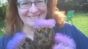 Lori poses with artichokes in bloom.