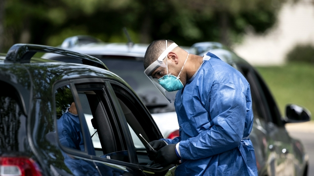 Man in a mask, face shield, and robe approaches a vehicle with a COVID-19 test