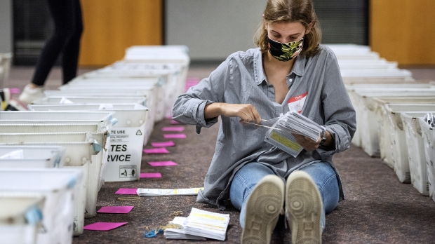 a woman sits on the floor next to rows of bins holding a large stack of ballots