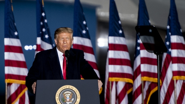 A line of U.S. flags can be seen behind Pres. Donald Trump as he speaks at a podium