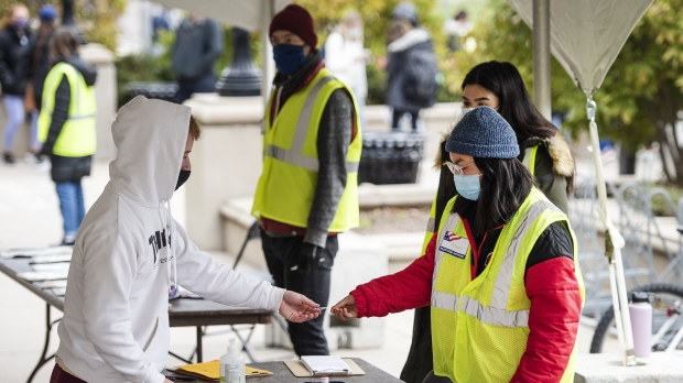 A poll worker hands a voter a sticker at an outdoor voting location