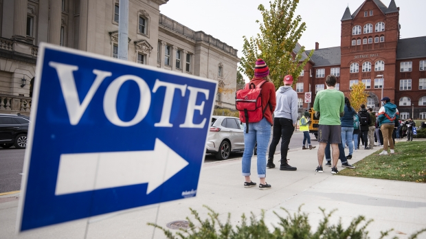 "A blue yard sign says ""VOTE"" near a line of early voters"
