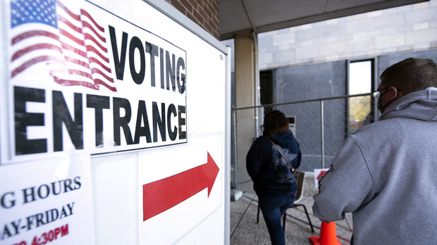 """A red arrow and a sign that says """"VOTING ENTRANCE"""" guides voters to the polling location"""