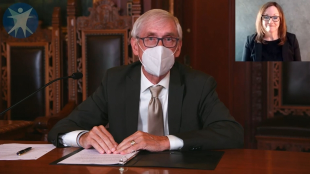 Governor Tony Evers addresses the public while wearing a mask