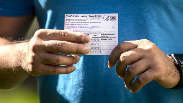 A white card with vaccine information is seen in someone's hands.