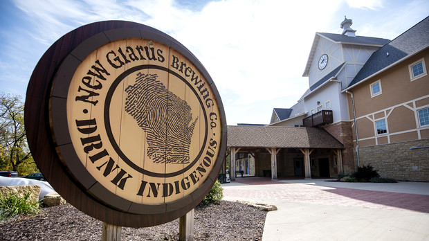 """A sign says """"New Glarus Brewing Co., Drink Indigenous"""" outside of the brewery."""