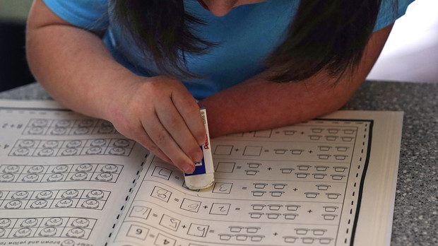 Lily Osgood, 7, corrects a math problem while studying at her family's home.