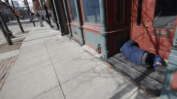 A homeless man sleeps in the doorway of an empty storefront
