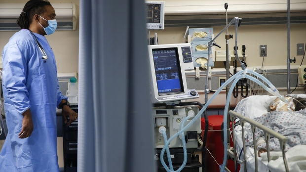 A nurse looks over at a COVID-19 patient who is attached to a ventilator