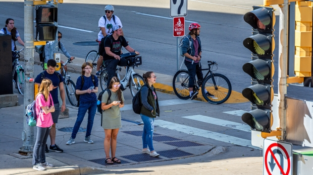 Students along University Ave. waiting to cross Park St. on the University of Wisconsin-Madison campus.
