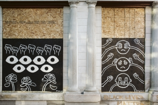 Artwork is displayed on boarded up store windows on State Street