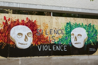 Artwork by Daniella Echeverría is displayed on boarded up store windows on State Street