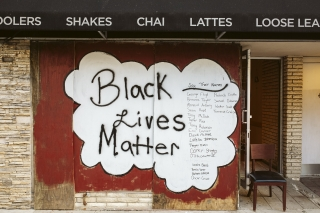 Artwork is displayed on boarded up store windows on State Street in downtown Madison