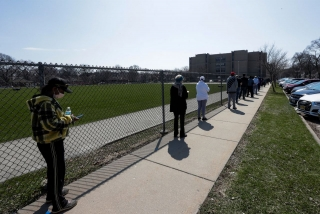 Voters wait to cast their ballots, practicing social distancing