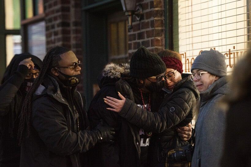 people embrace on a sidewalk