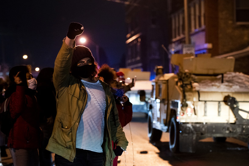 military style vehicles drive by as a protester raises a fist