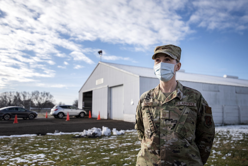 A woman in a military uniform stands near a barn that has been repurposed as a drive-thru testing site