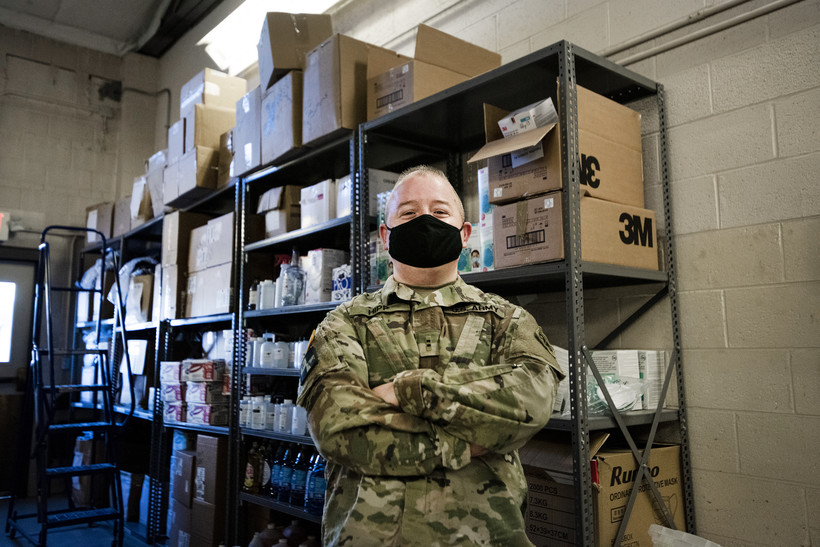 a man in a military uniform and a black face mask stands near shelves of PPE with his arms crossed