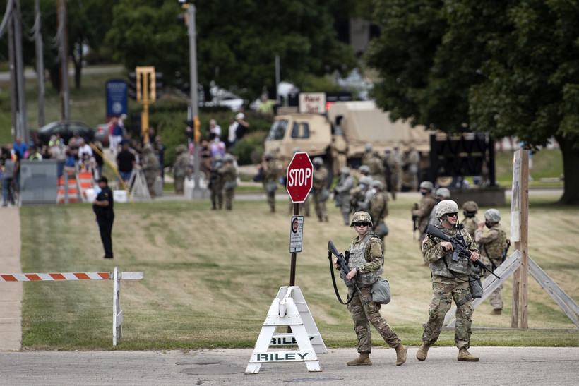 A line of Wisconsin National Guard members form a line outside of a high school