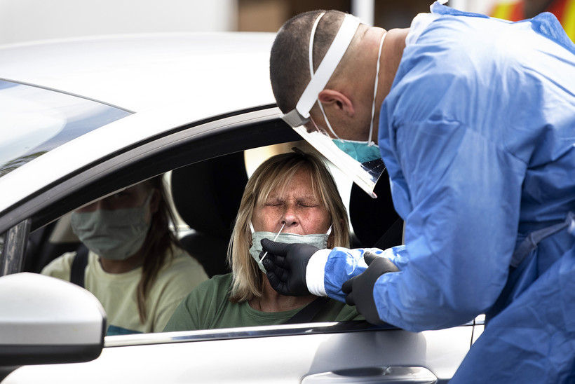 A woman's nose is swabbed while receiving a COVID-19 test at a drive thru location