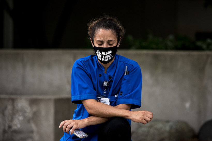 """A woman in a mask that says """"Black Lives Matter"""" closes her eyes"""