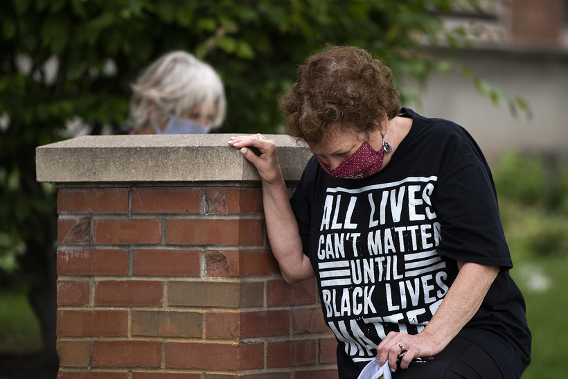 "A woman kneels while wearing a shirt that says ""All lives can't matter until black lives matter"""