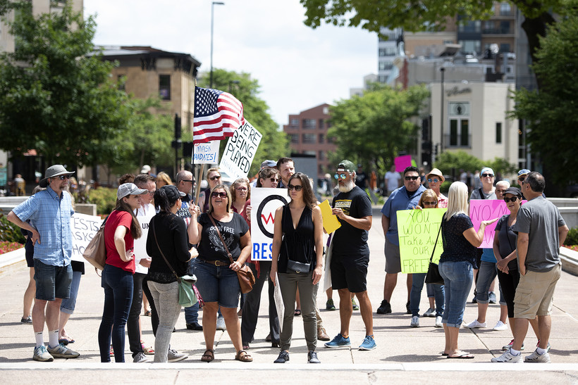 protesters hold signs and an American flag