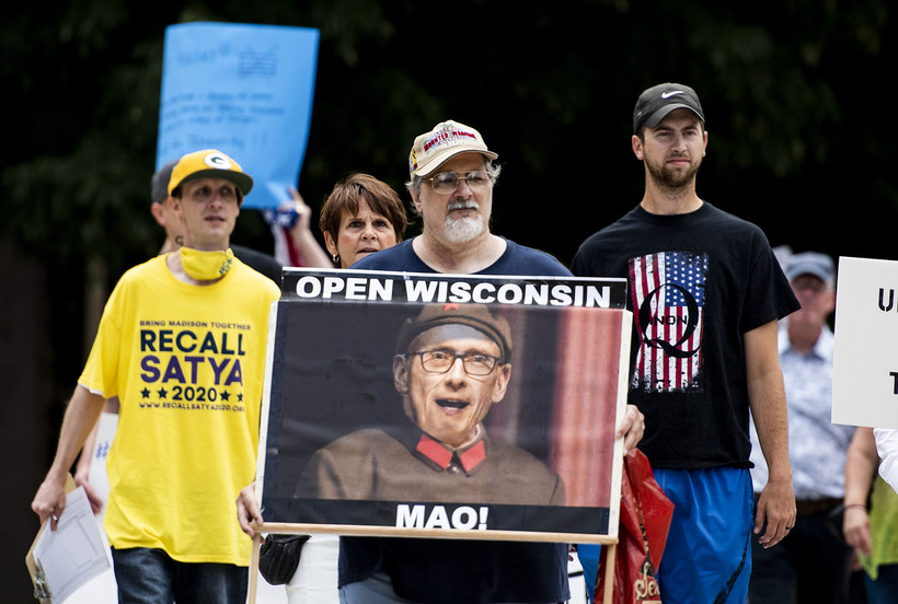 A man holds a sign that compares Gov. Evers to Mao