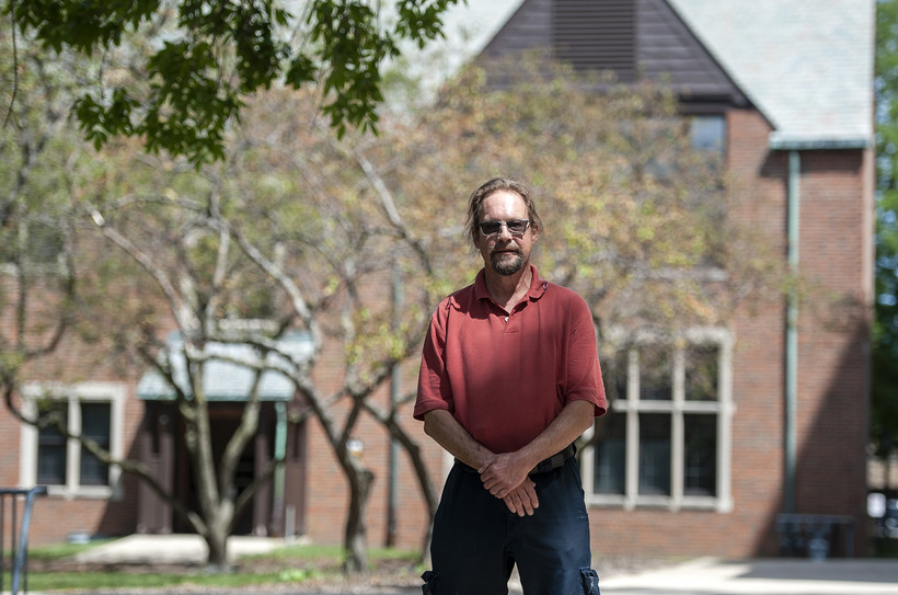 A man stands in front of a large brick building
