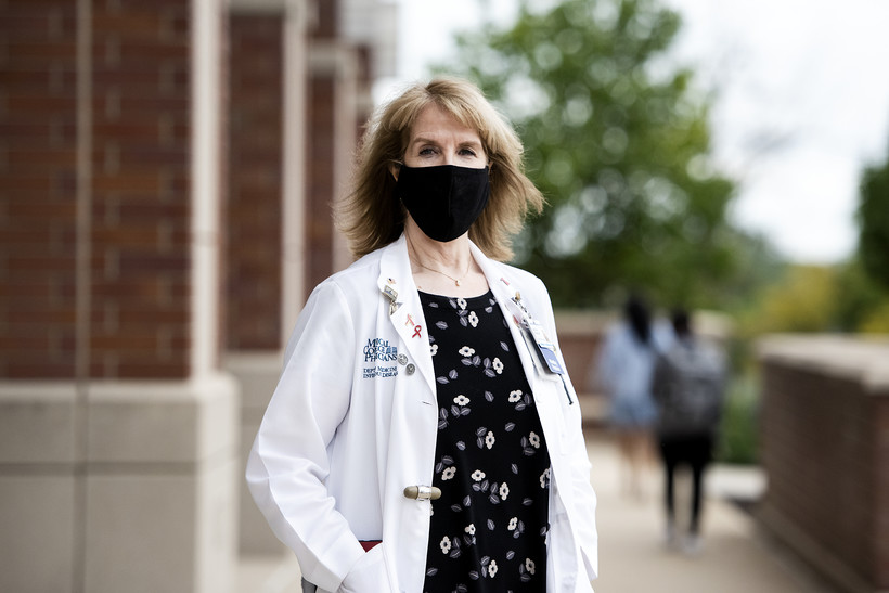 A woman in a white coat and black face mask stands outside as people walk past