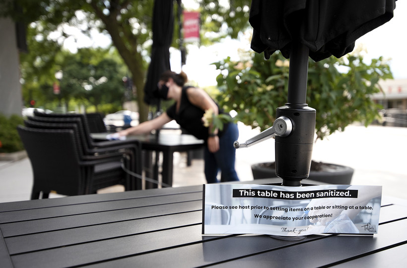 """A sign says """"this table has been sanitized."""" a woman is seen in the background wiping down a table."""
