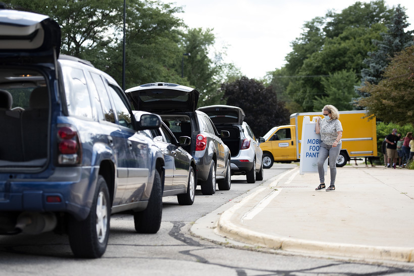 a line of cars with trunks open wait in front of the school as a volunteer walks by with a sign