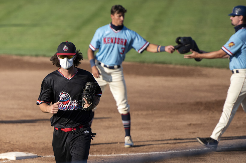 a baseball player in a mask runs off the field as players behind him interact