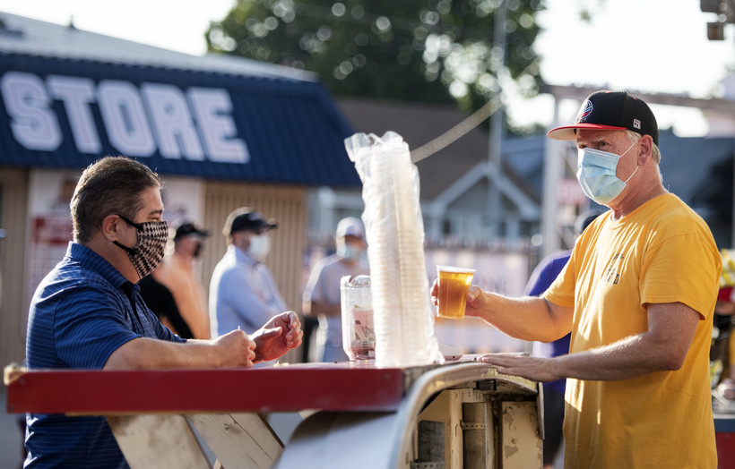 a man in a mask serves beer at an outdoor tap to a customer in a mask