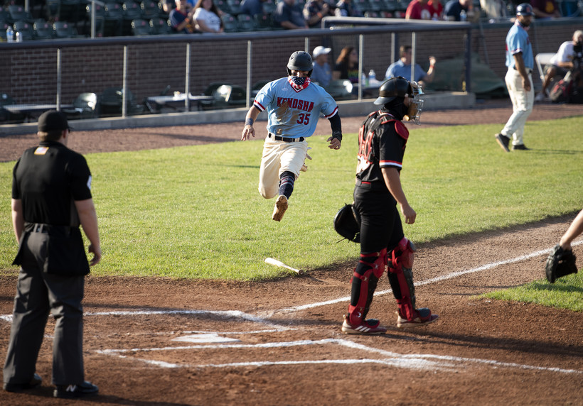 a baseball player in a mask leaps to home plate