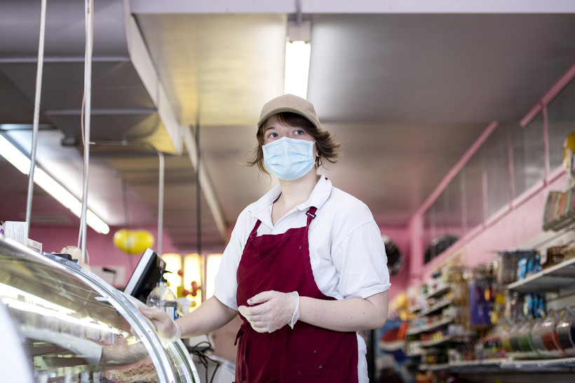 A worker in a face mask wipes down the display of fudge in a candy shop with pink walls