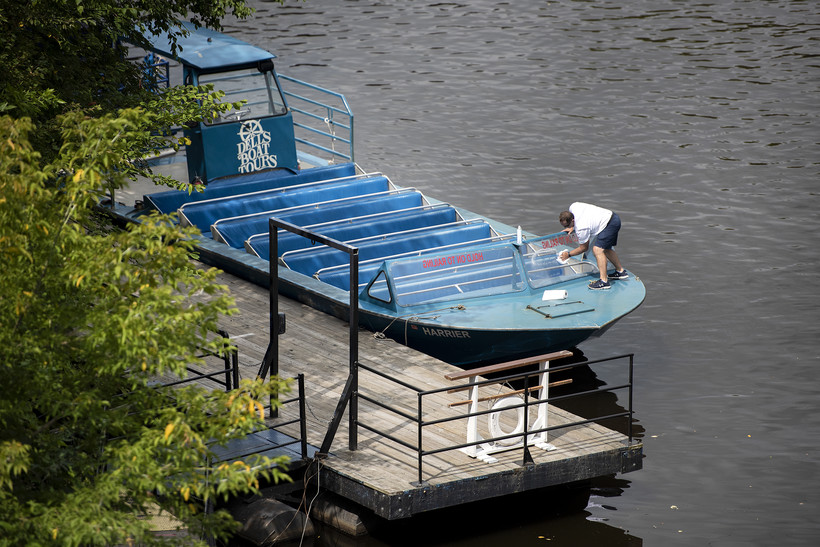 seen from up high, a man wipes the front glass of a parked tour boat