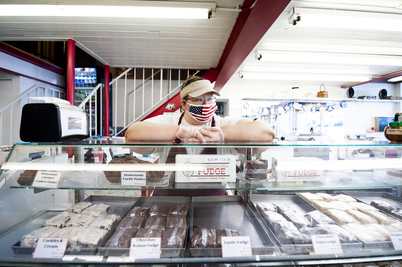 a woman in an American flag face mask puts her arms up on a display of fudge