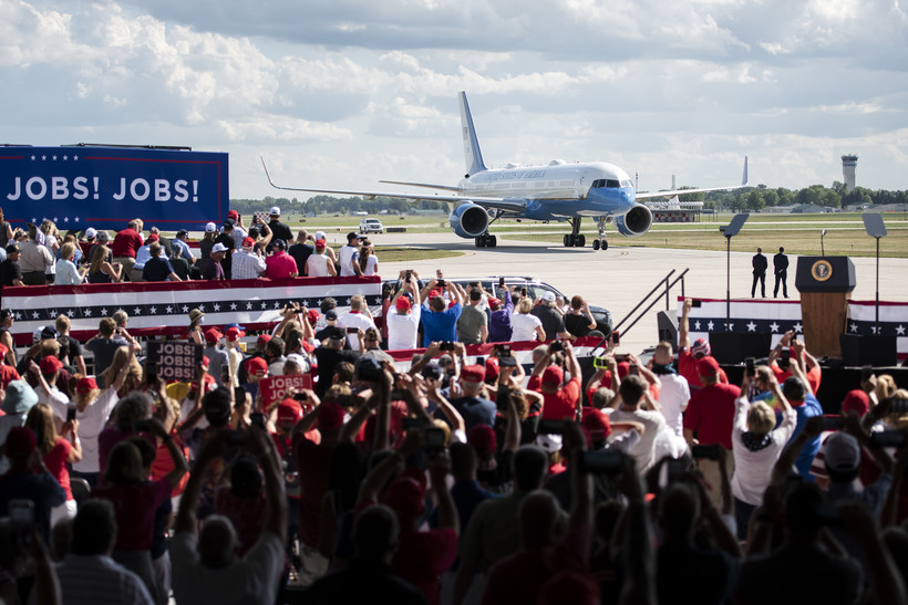 the crowd cheers as Air Force one drives up on the runway