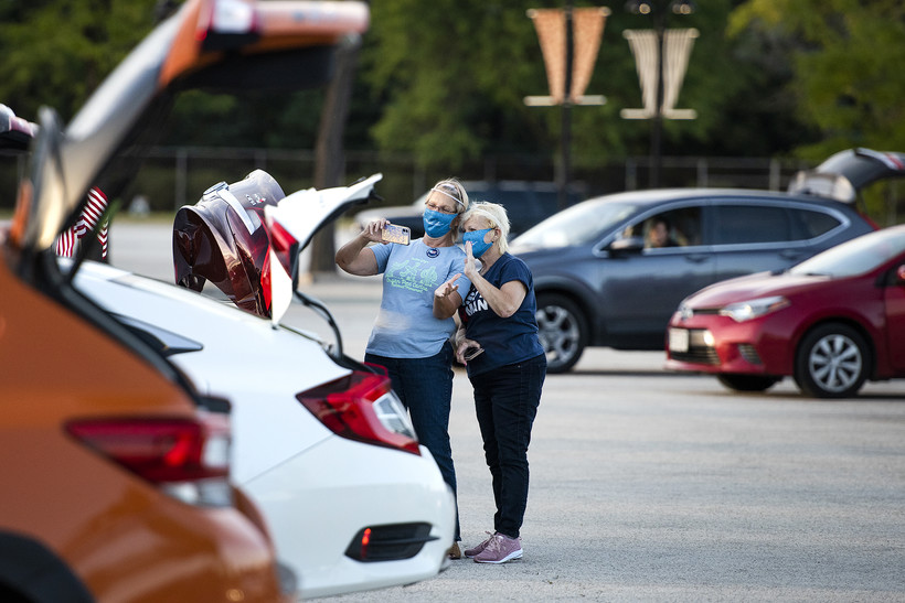 Two ladies in face masks stand near parked cars as they take a selfie together