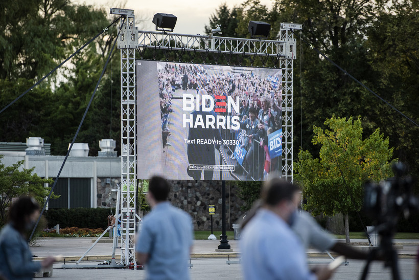 "A large screen shows the words ""Biden Harris"" during a promotional video"