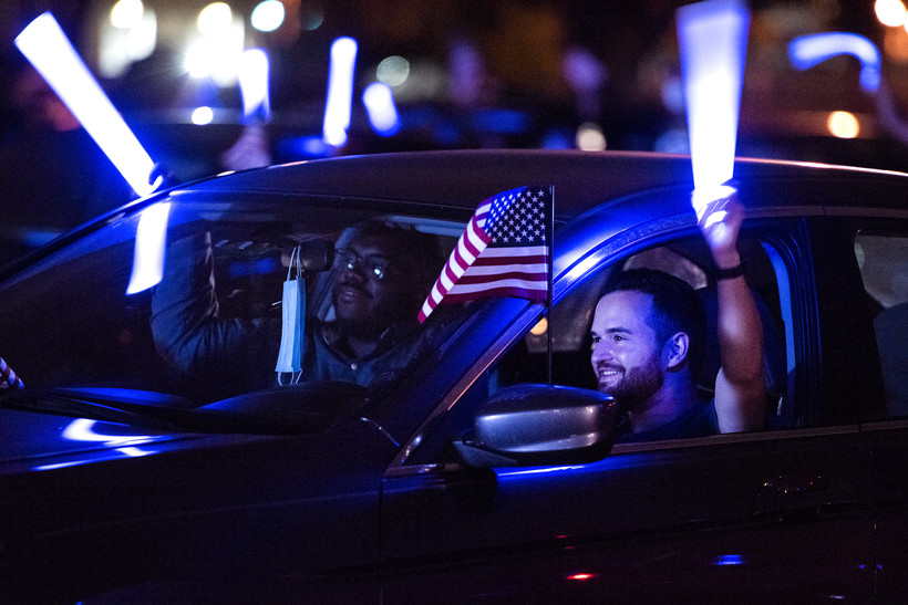 Blue light from a light stick illuminates a smiling man holding an American flag inside his car
